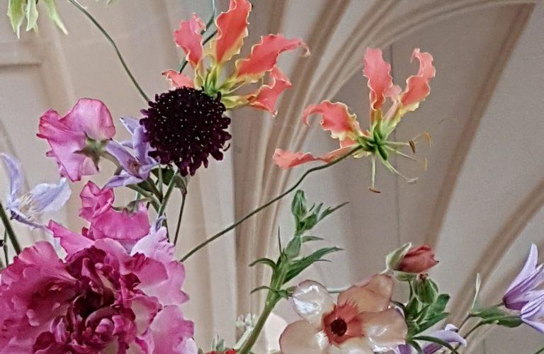 Japanische Ranunkeln, Gloriosen, Clematis, in Froschperspektive vor gothischem Gewölbe
